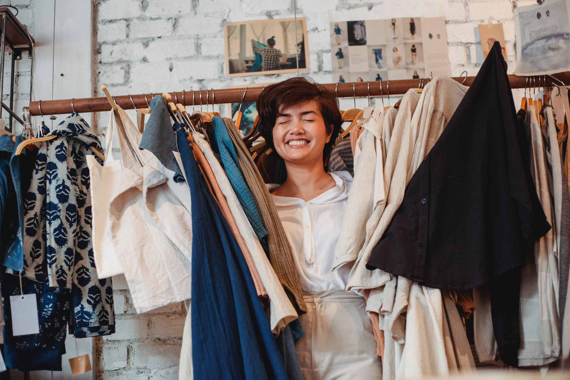 cheerful asian female customer standing among hanging clothes in store and smiling