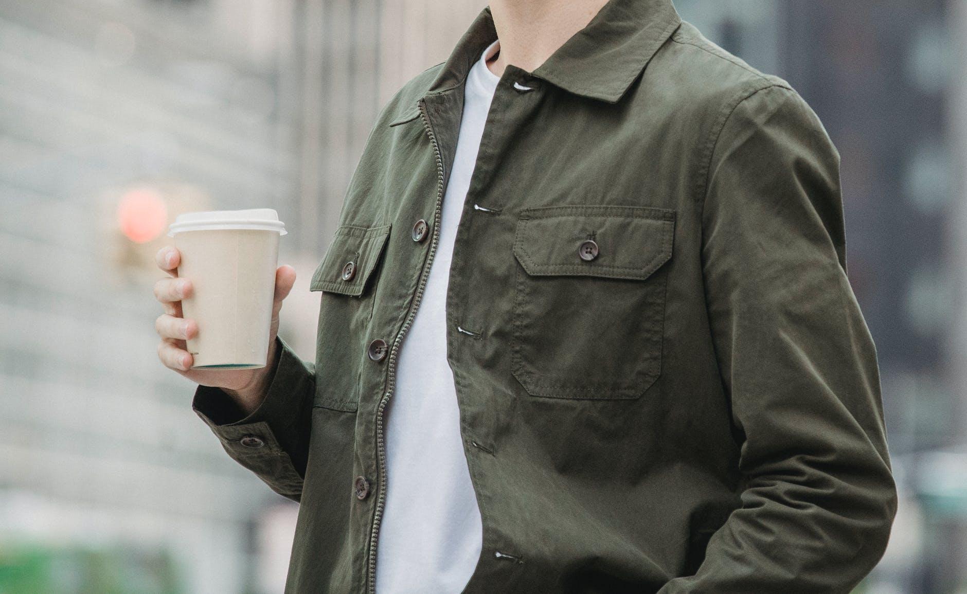 unrecognizable man drinking takeaway coffee in downtown