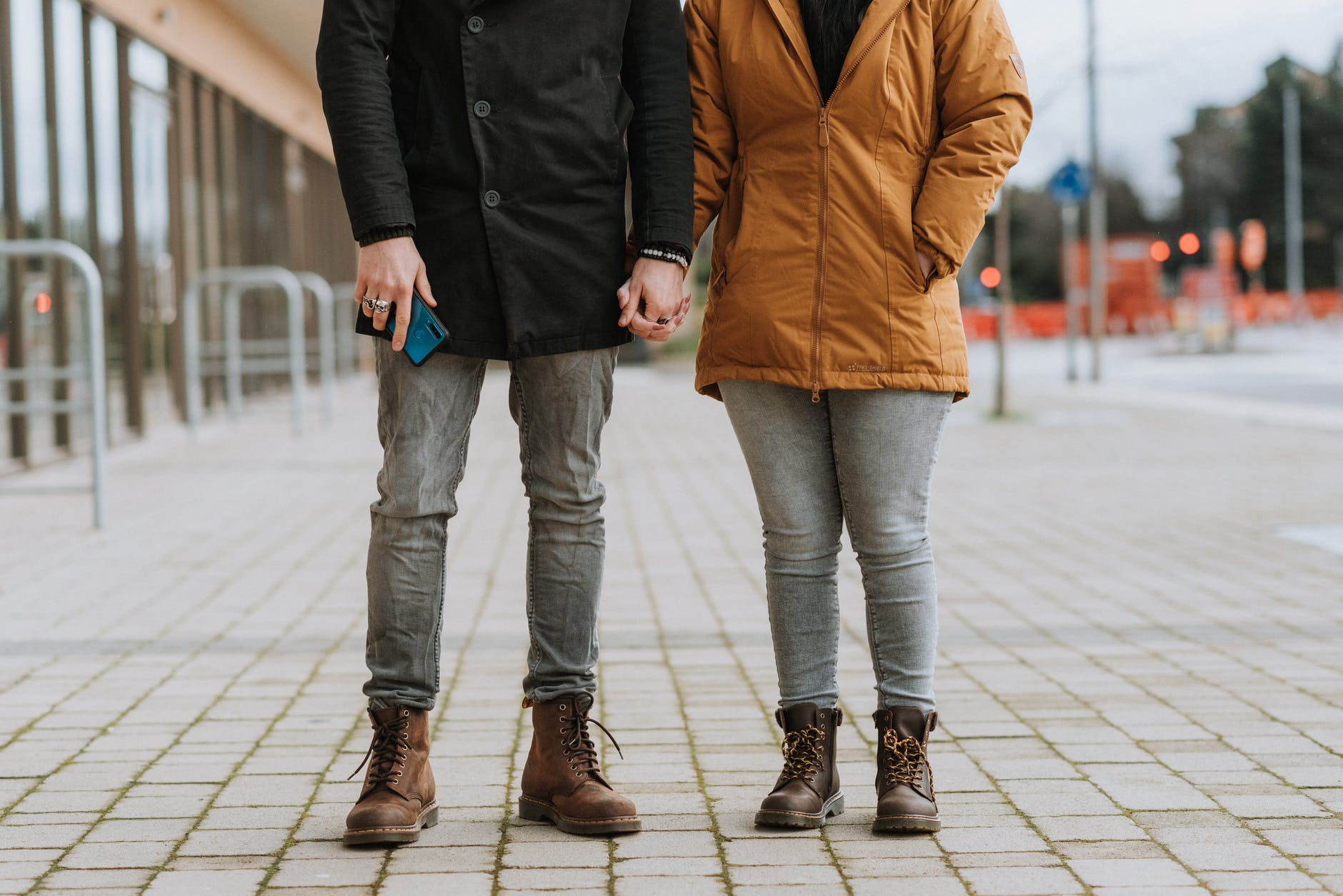 unrecognizable couple holding hands on street