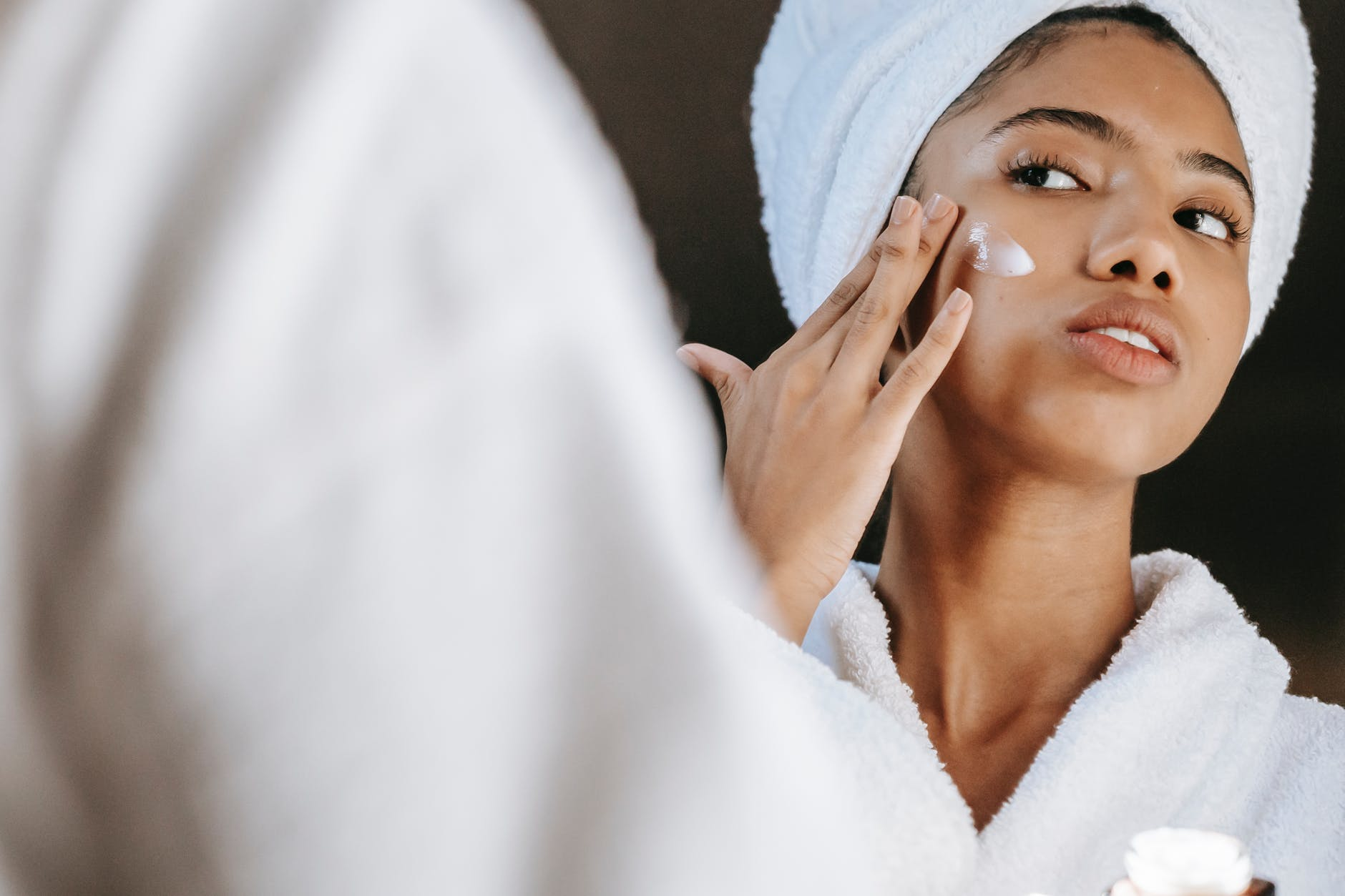 ethnic woman applying cream on face in morning
