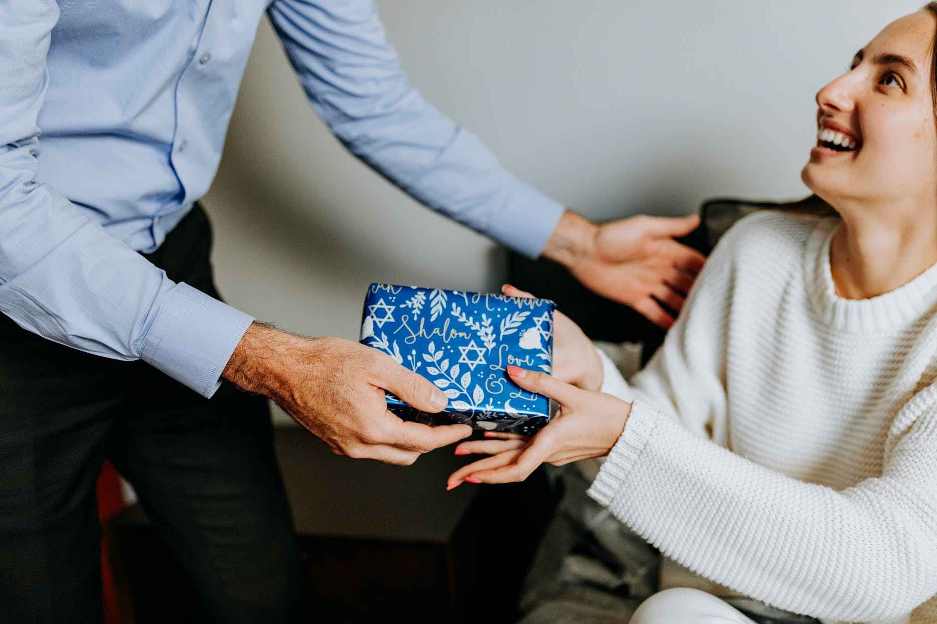 photo of person handing gift to woman